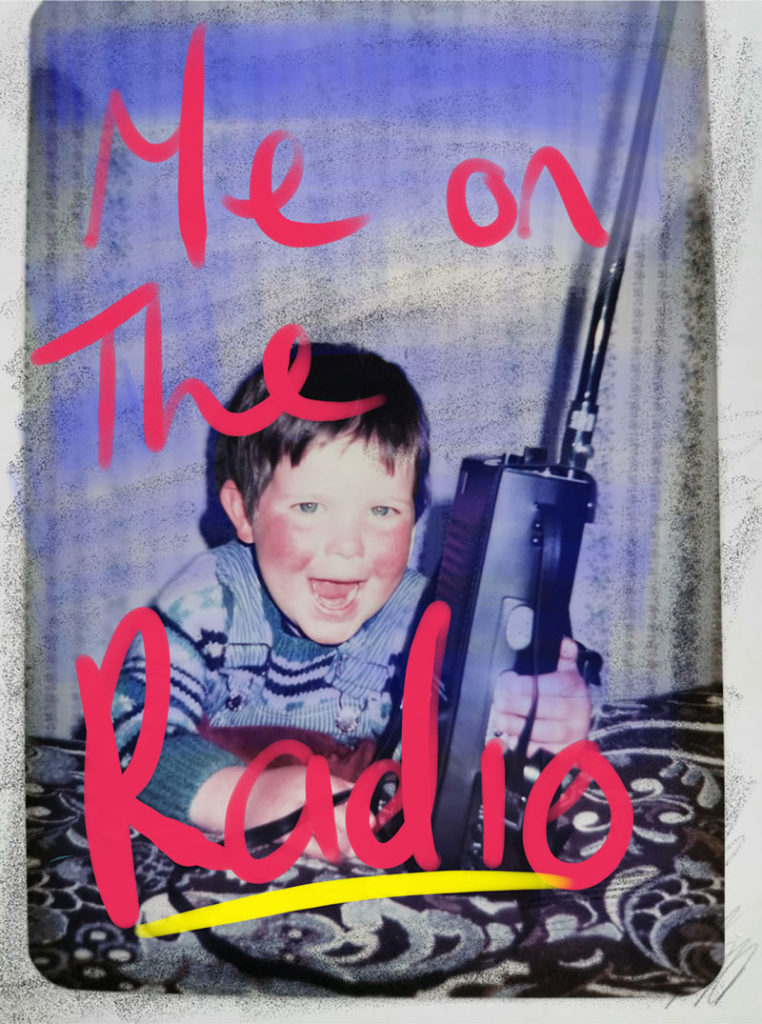 A small ruddy-faced boy holding a massive CB radio and grinning maniacally